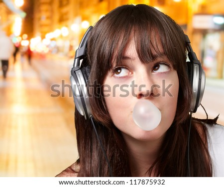 portrait of young woman listening to music with bubble gum at night city - stock photo