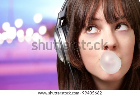 portrait of young woman listening to music with bubble gum over abstract lights - stock photo