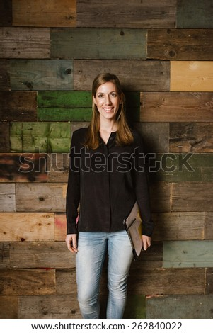 Portrait of young woman looking happy while posing for camera against a wooden wall in office. Young business executive in office. - stock photo