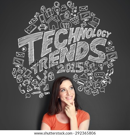 portrait of young woman looking up thinking about new technology trends on 2015 - stock photo