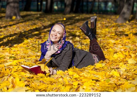 Portrait of young woman lying on autumn leaves with book in autumn park