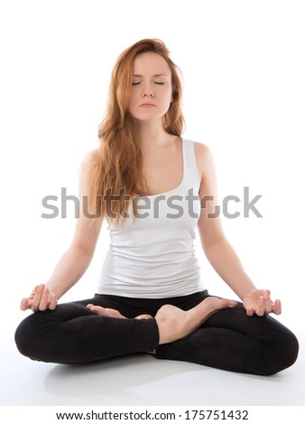 Portrait of young woman meditating in yoga pose of lotus on a white background - stock photo
