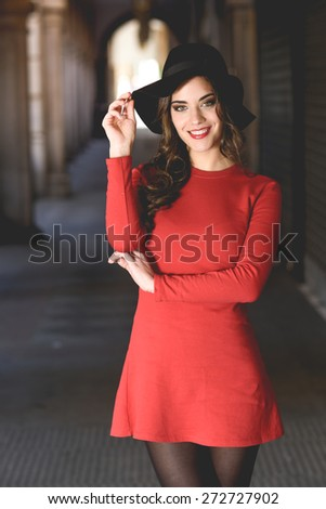 Portrait of young woman, model of fashion, smiling in urban background wearing red dress and hat - stock photo