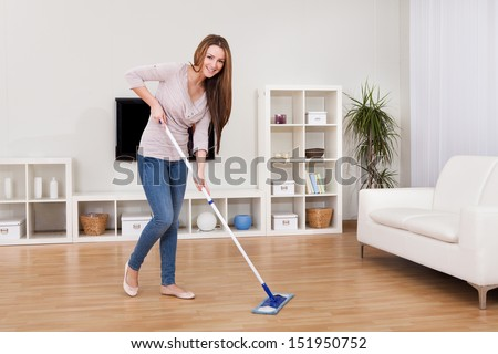 Portrait Of Young Woman Mopping Floor At Home - stock photo