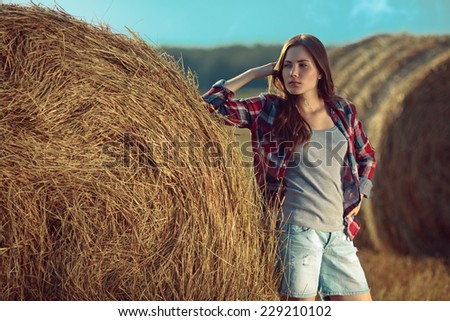 Portrait of young woman next to a stack of hay - stock photo