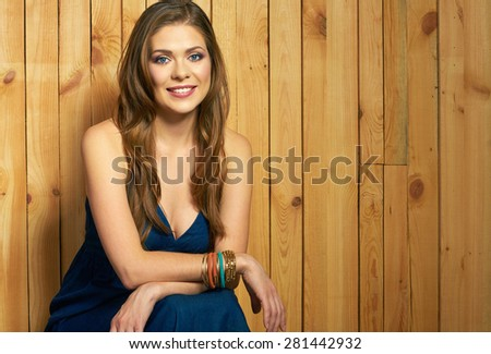 Portrait of young woman on wood background. Toothy smiling girl portrait. Beautiful female model posing. Long hair.