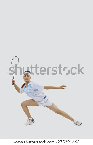 Portrait of young woman playing badminton isolated over gray background