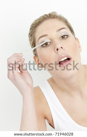 portrait of young woman putting on eye shadows - stock photo