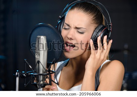 Portrait of young woman recording a song in a professional studio - stock photo