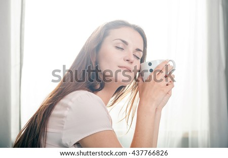 Portrait of young woman relaxing at home and drinking coffee, casual style indoor shoot - stock photo