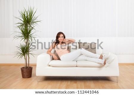 Portrait Of Young Woman Relaxing On Sofa At Home. - stock photo