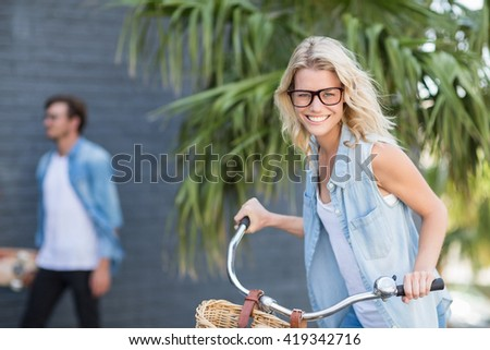 Portrait of young woman riding bicycle smiling - stock photo