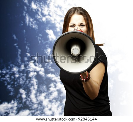 portrait of young woman shouting with megaphone against a cloudy sky background