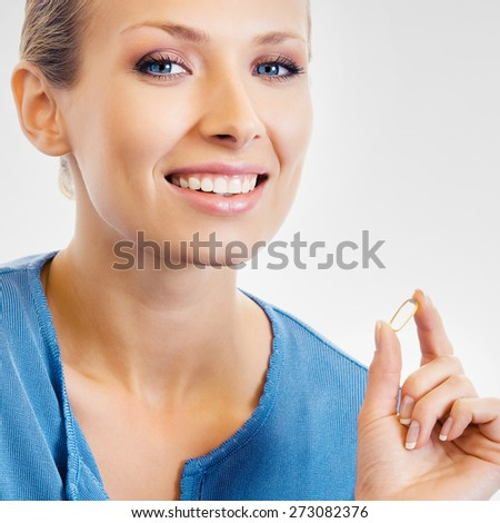Portrait of young woman showing Omega 3 fish oil capsule, over grey background - stock photo