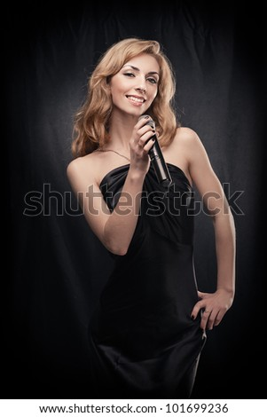 Portrait of young woman singer holding microphone over black background - stock photo