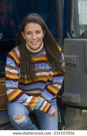Portrait of young woman sitting in van - stock photo