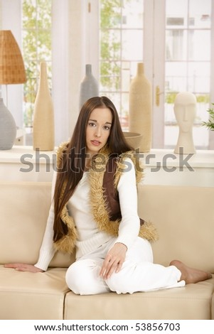 Portrait of young woman sitting on couch, relaxing in living room.
