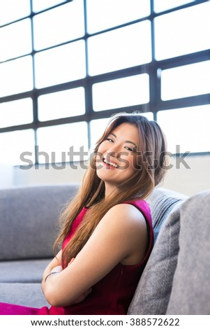 Portrait of young woman sitting on sofa in office - stock photo