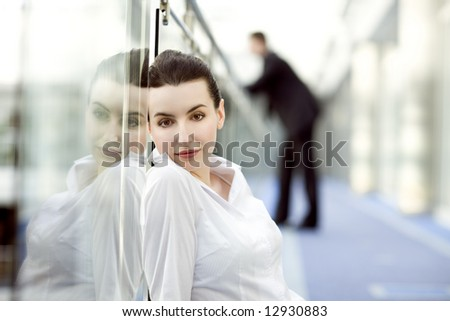 Portrait of young woman sitting on the floor in modern office building corridor and leaning against glass balustrade - stock photo