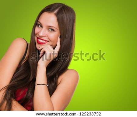 Portrait Of Young Woman Smiling against a green background - stock photo