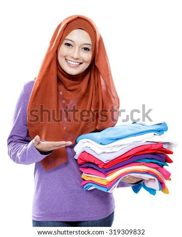portrait of young woman smiling and presenting clean clothes after ironing isolated on white background - stock photo