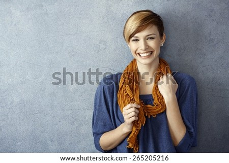 Portrait of young woman smiling happily standing by wall. Copy space. - stock photo