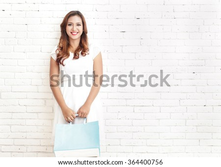 portrait of young woman smiling while carrying shopping bags with white brick wall on the background with copyspace - stock photo