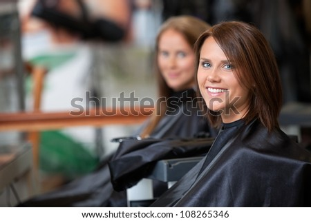 Portrait of young woman smiling with female customer in background at parlor