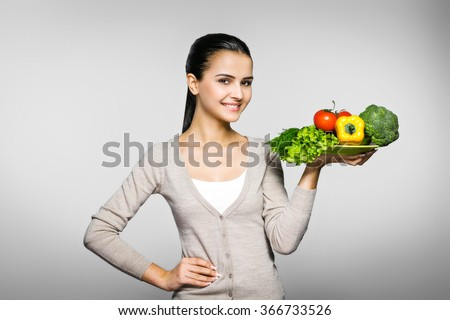 Portrait of young woman standing against grey background. Woman holding plate of fresh vegetables and looking at camera. Concept for healthy food - stock photo