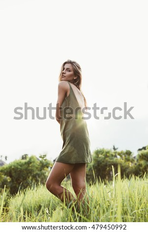 Portrait of young woman standing in field of grass. Beautiful female fashion model posing outdoors on a summer day.