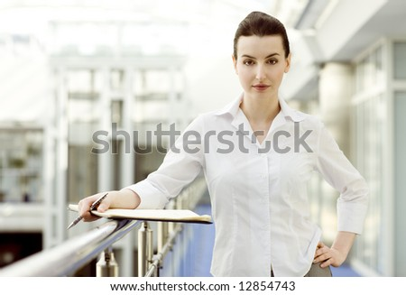 Portrait of young woman standing with calendar - stock photo