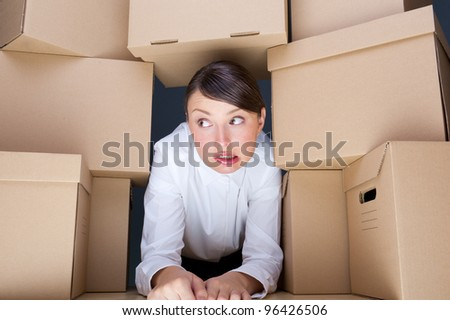 Portrait of young woman surrounded by lots of boxes. Lots of work concept. - stock photo