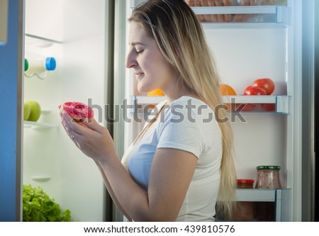 Portrait of young woman taking donut from refrigerator at night - stock photo