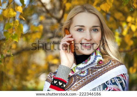 Portrait of young woman talking on mobile phone in autumn park - stock photo