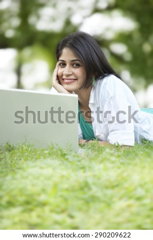 Portrait of young woman using laptop while lying on grass