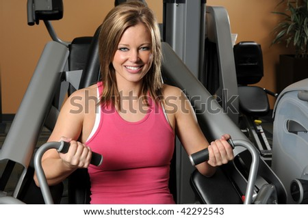 Portrait of young woman using weight machine at a gym