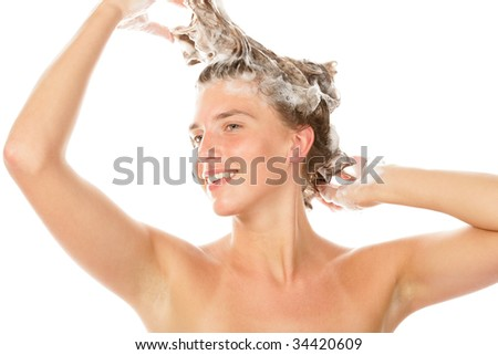 Portrait of young woman washing hair isolated on white background - stock photo