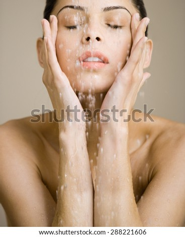 portrait of young woman washing her face with clean water - stock photo