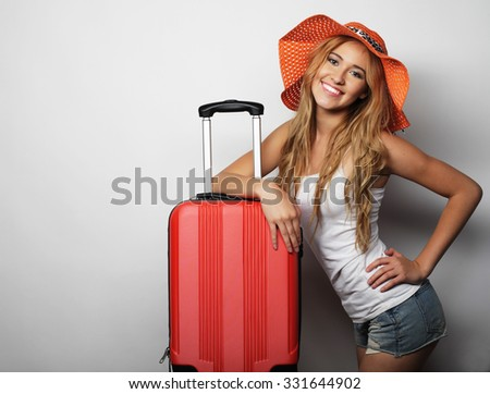 Portrait of  young woman wearing big straw orange hat  standing with orange travel bag - stock photo