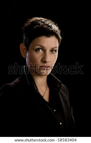 Portrait of young woman wearing black shirt, isolated on black. - stock photo