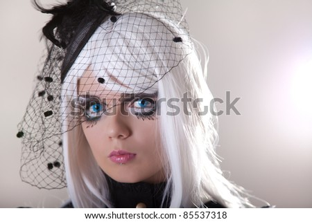 Portrait of young woman wearing blue contact lenses, studio shot - stock photo