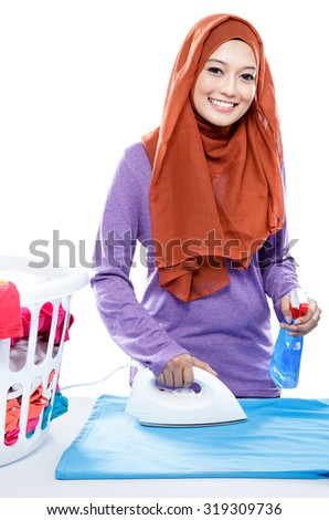 portrait of young woman wearing hijab ironing clothes and spraying perfume isolated on white - stock photo