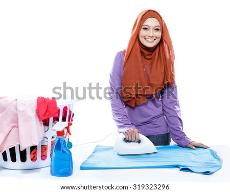 portrait of young woman wearing hijab ironing clothes isolated on white - stock photo