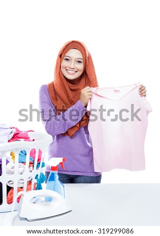 portrait of young woman wearing hijab ironing while pick up a clothes isolated on white background - stock photo