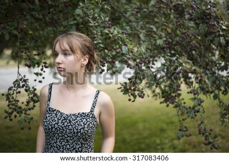 Portrait of young woman wearing summer dress outside under crabapple tree looking away with copy space - stock photo