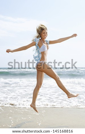 Portrait of young woman with arms outstretched jumping at beach - stock photo