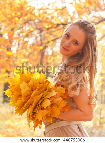 Portrait of young woman with autumn leaves in hand and fall yellow maple garden background