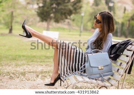 Portrait of young woman with beautiful legs in urban park wearing casual clothes. Girl wearing striped skirt, sweater, sunglasses and high heels - stock photo
