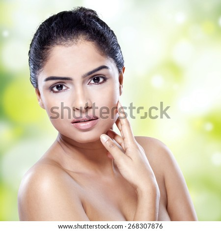 Portrait of young woman with black hair, pretty face, and perfect skin looking at camera against bokeh background