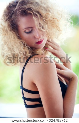 Portrait of young woman with blond curly hair, red lips and black eyeliner, hands with red nails, outdoors on sunny day - stock photo